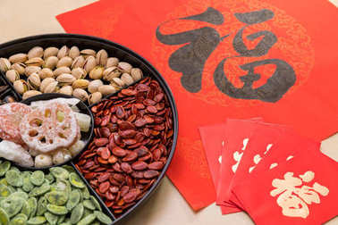 Chinese snack tray with red packets and Chinese calligraphy word means luck