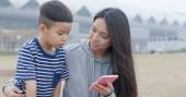 Fotografia Madre utilizzando smartphone con suo figlio