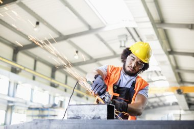Worker using grinder on metal in factory