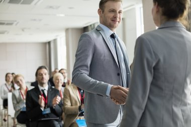 Businessman greeting public speaker during seminar