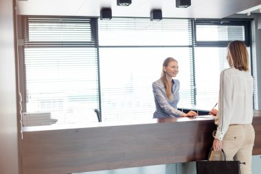 Happy receptionist talking with businesswoman