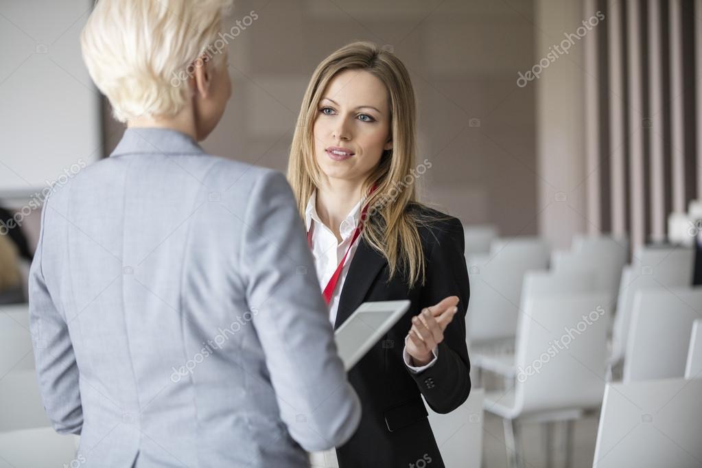 Businesswomen discussing in seminar hall