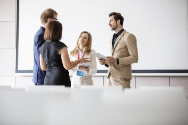 Business people discussing in seminar hall
