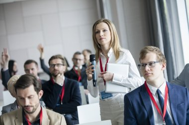 Businesswoman asking questions during seminar