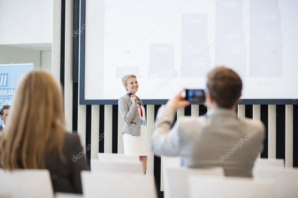 businessman photographing public speaker
