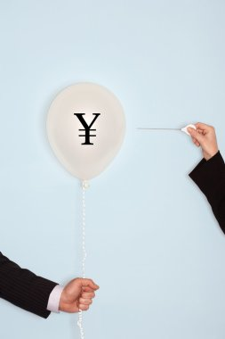hands holding balloon with yuan sign