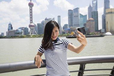 woman taking selfie against Pudong skyline