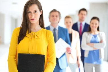 businesswoman with team in background at office
