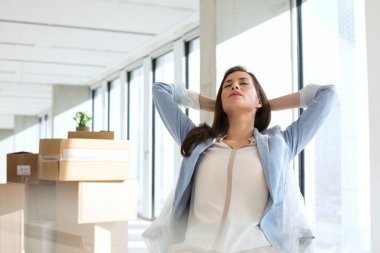 Relaxed businesswoman with hands behind head