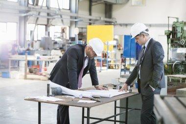 Businessmen examining blueprint at workbench