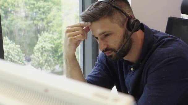 Sad man in headset in office