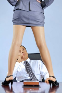 Businesswoman standing on table in front of businessman
