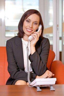 Businesswoman conversing on landline phone