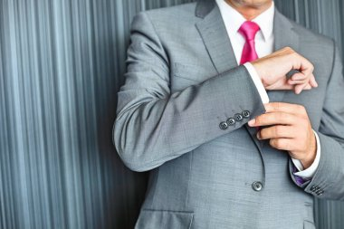 Mature businessman buttoning sleeve
