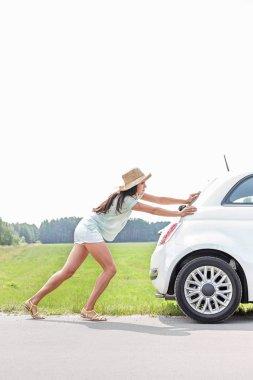 woman pushing broken down car