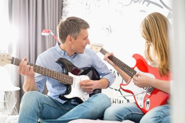 Man with daughter playing guitars