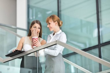 Businesswomen gossiping while having coffee