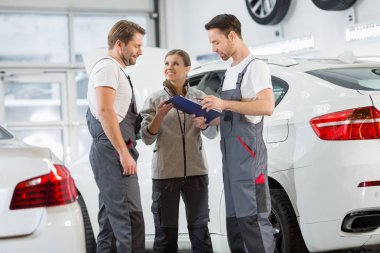 Automobile mechanics discussing over clipboard