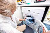 Fotografie Senior woman loading washing machine