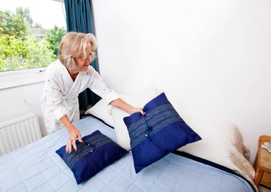 Senior woman arranging cushions