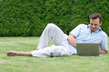 Man using laptop while lying on grass