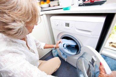 Senior woman loading washing machine