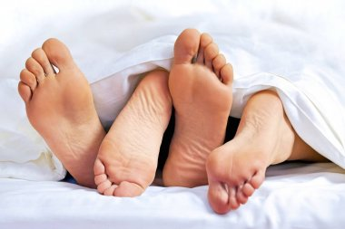 feet of a couple on the bed