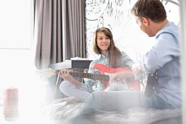 Girl with father playing electric guitars