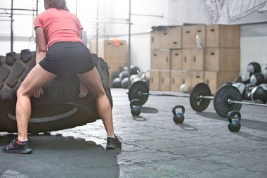woman flipping tire in crossfit gym