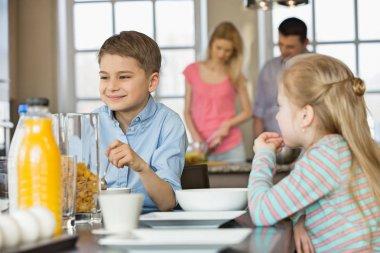 Siblings having breakfast at table