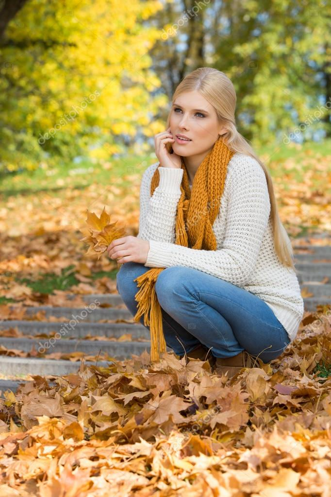 woman crouching on steps in park