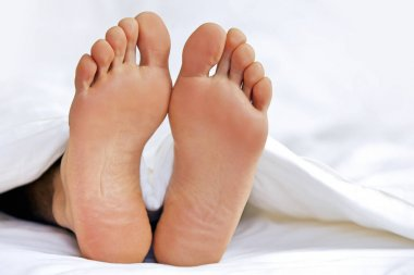 Person's feet in bed