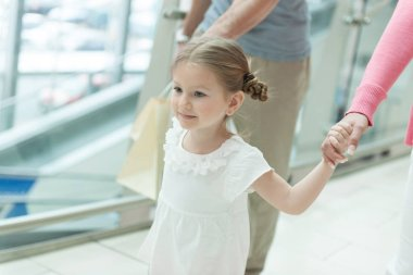 Girl holding parents hands