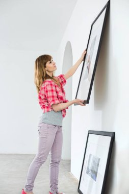 Woman hanging picture frame