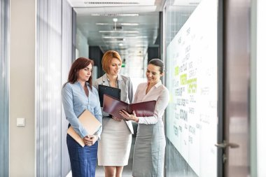 Businesswomen with file folders discussing