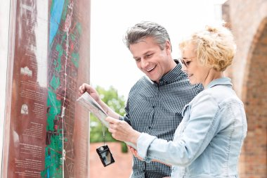 Couple reading map in city