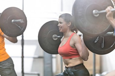 woman lifting barbell in crossfit gym