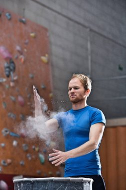 Man dusting powder by climbing wall