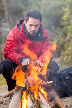 hiker warming his hands at campfire