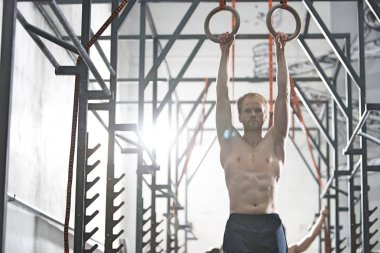 Confident man exercising with gymnastic rings