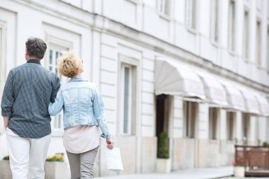 middle-aged couple walking by building
