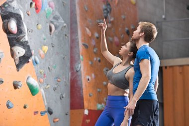 Man and woman discussing by climbing wall