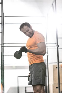 man lifting kettlebell in crossfit gym