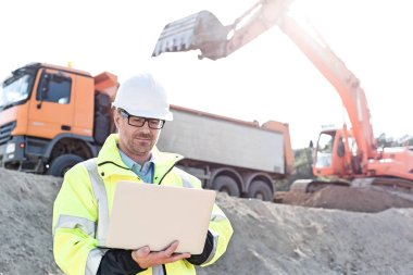 Supervisor using laptop at construction site