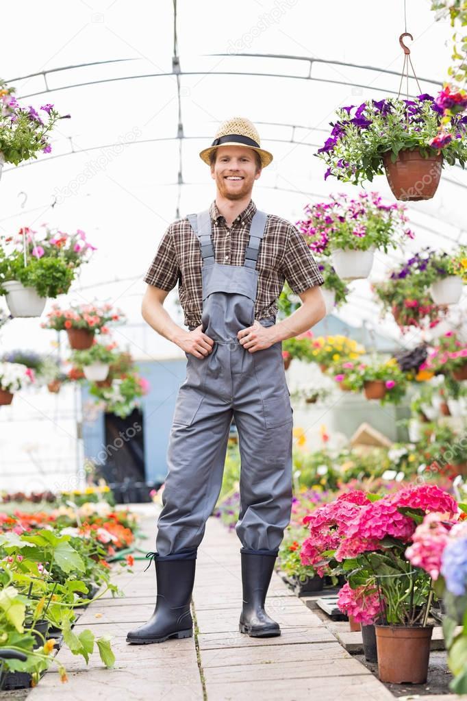 Happy gardener standing at greenhouse