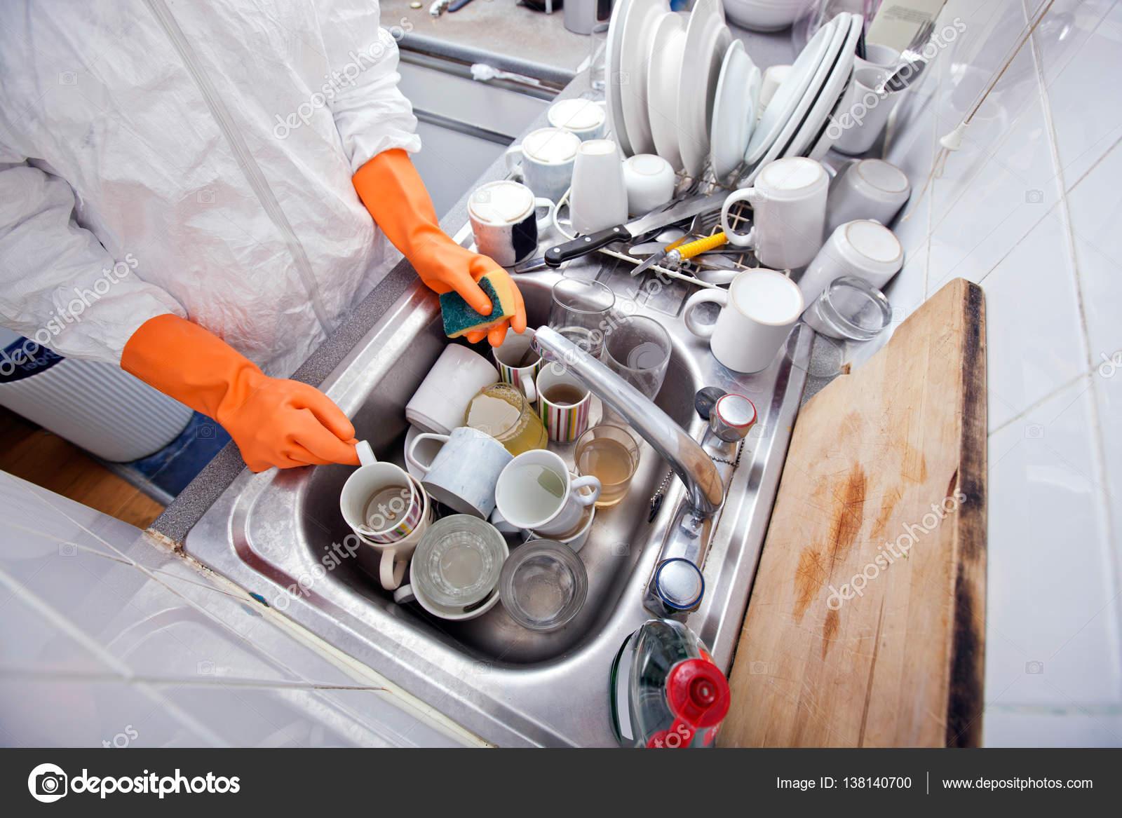 mujer de las manos en los guantes de lavar utensilios de