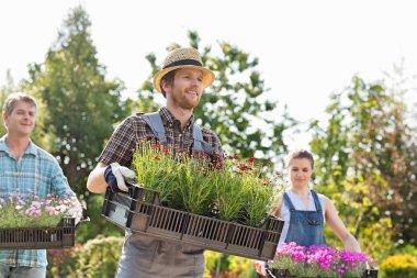 Gardeners carrying flower pots
