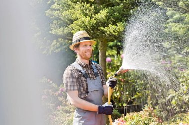 Happy man watering plants