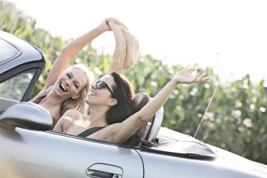 Excited female friends on road trip