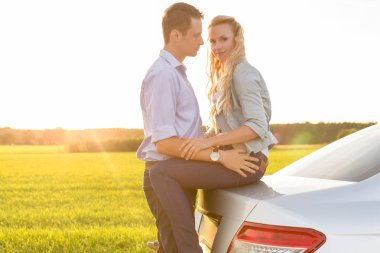 romantic couple by car at countryside